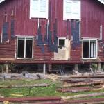 Bostadshus under pågående renovering, ståendes på lyftstolpar.